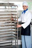 Chef moving tray rack towards corner — Stock Photo