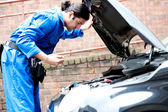 Mechanic checking the motor oil of the car — Stock Photo