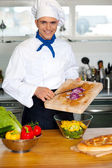 Chef putting vegetables in a bowl — Stock Photo