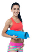 Woman gym instructor holding blue mat — Stock Photo