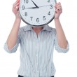 Woman hiding her face behind wall clock — Stock Photo