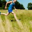 Young man running through meadows — Stock Photo