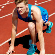 Young male sprinter in starting blocks — Stock Photo #32582837