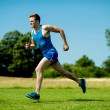 Stockfoto: Fit athlete running hard on sunny day