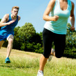 Stock Photo: Two athletes running through meadows