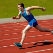 Young caucasian athlete sprinting on track — Stock Photo #32583323
