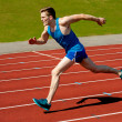 Young caucasian athlete sprinting on track — Stock Photo