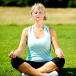 Woman meditating outdoors on a sunny day — Stock Photo #32583391