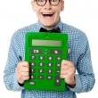 Young nerd showing big green calculator — Stockfoto