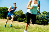 Two athletes running through meadows — Stock Photo