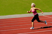 Athletic kvinna körs på spår — Stockfoto