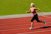 Atlética mulher correndo na pista — Foto Stock