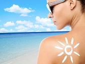 Young woman with suntan lotion on her back — Stockfoto
