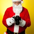 Santa checking pictures on his DSLR camera — Stockfoto