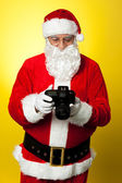 Santa checking pictures on his DSLR camera — Stock Photo