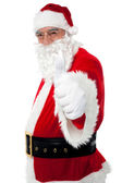 Happy santa gesturing thumbs up — Stock Photo