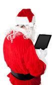 Santa using touch pad — Stockfoto