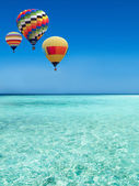 Hot air balloons travel over the sea — Stock Photo