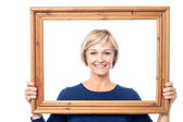 Middle aged lady holding photo frame — Stock Photo