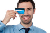 Businessman hiding his eye with credit card — Stock Photo