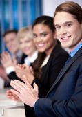 Corporate team sitting in a row and applauding — Stock Photo