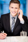 Smiling corporate guy attending phone call — Zdjęcie stockowe