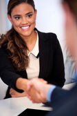 Businesswoman shaking hands with a client — Stock Photo
