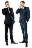 Two businessmen talking on cellphone — Stock Photo