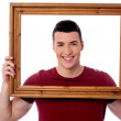 Man holding wooden picture frame — Stock Photo