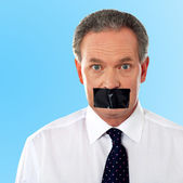Businessman with tape on his mouth — Stock Photo
