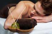 Young man relaxing on massage table — Stock Photo