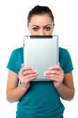 Shy pretty model hiding face with tablet pc — Stock Photo