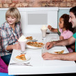 Cheerful family of four enjoying breakfast — Stock Photo
