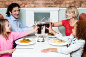 Family raising their glasses before eating — Stock Photo