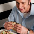 Man eating sandwich in a restaurant — Stock Photo
