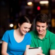 Couple using digital tablet in cafe — Stock Photo