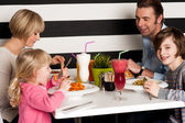 Family toasting smoothies in restaurant — Stock Photo