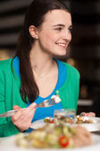 Happy young girl enjoying her dinner — Stock Photo