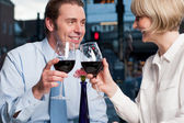 Happy couple raises a glass of red wine — Stock Photo