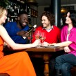 Four friends enjoying dinner at a restaurant — Stock Photo