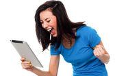 возбужденный молодая девушка, держа устройство touch pad — Стоковое фото