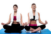 Two young girls doing yoga at gym — Stock Photo