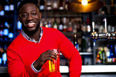 African guy posing with chilled beer — Stock Photo