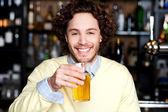 положительный молодой человек, держа бокал пива — Стоковое фото
