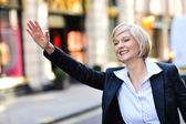 Businesswoman raising her arm to call a taxi — Stock Photo