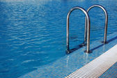 Swimming pool with steel ladder — Stock Photo