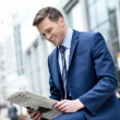 Smiling businessman reading paper at outdoors — Stock Photo #44785225