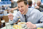 Smiling young businessman having lunch — Stock Photo