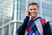 Casual male executive talking via mobile phone — Stock Photo