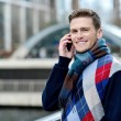 Handsome man using mobile at bridge railing — Stock Photo